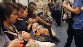 Μπανγκόκ, Ταϊλάνδη - 21 Οκτωβρίου 2017: Άνθρωποι που χρησιμοποιούν τα έξυπνες τηλέφωνα και τις συσκευές μέσα στο βαγόνι εμπορευμά απόθεμα βίντεο