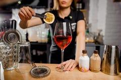 Μπαργούμαν που προσθέτει στη φέτα κοκτέιλ του λεμονιού που χρησιμοποιεί τις λαβίδες Στοκ εικόνα με δικαίωμα ελεύθερης χρήσης