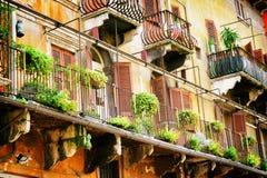 Μπαλκόνια του παλαιού σπιτιού που διακοσμούνται με τα λουλούδια στη Βερόνα, Ιταλία Στοκ εικόνες με δικαίωμα ελεύθερης χρήσης