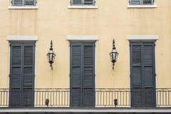 Μπαλκόνι γαλλικών συνοικιών με τις πόρτες και τους λαμπτήρες Στοκ Εικόνα