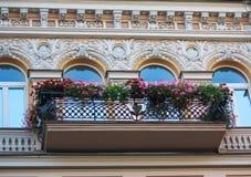 Μπαλκόνι με τα λουλούδια και την πρόσοψη του κτηρίου κλασσικό σε styleBalcony με τα λουλούδια και την πρόσοψη του κτηρίου Στοκ Φωτογραφίες