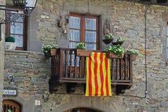 Μπαλκόνι με την άσπρη πετούνια και καταλανική σημαία σε Rupit Καταλωνία, Ισπανία Στοκ Εικόνα