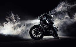 Μπαλτάς μοτοσικλετών υψηλής δύναμης με τον αναβάτη ατόμων τη νύχτα στοκ εικόνες