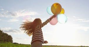 Μπαλόνια αέρα στα χέρια του παιχνιδιού μικρών κοριτσιών που χορεύει υπαίθρια σε σε αργή κίνηση φιλμ μικρού μήκους