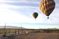 Μπαλόνια ζεστού αέρα που πετούν στα ύψη πέρα από τα οδοστρώματα Στοκ Φωτογραφία