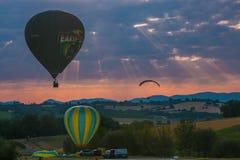 Μπαλόνια και ανεμόπτερο ζεστού αέρα που πετούν στην ανατολή στην Ουμβρία Στοκ Εικόνες