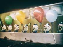 Μπαλόνια παιχνιδιών καρναβαλιού κλόουν πυροβόλων όπλων νερού αναδρομικά στοκ εικόνες