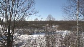 Μπαλόνι ζεστού αέρα που πετά κατά τη χειμερινή άποψη μπλε ουρανού απόθεμα βίντεο