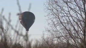Μπαλόνι ζεστού αέρα που πετά κατά τη χειμερινή άποψη μπλε ουρανού φιλμ μικρού μήκους