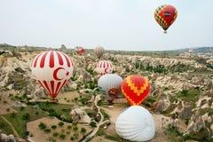 Μπαλόνι ζεστού αέρα που πετά πέρα από το τοπίο βράχου σε Cappadocia Τουρκία Στοκ Εικόνες