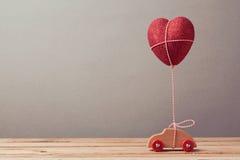Μπαλόνι μορφής καρδιών και παιχνίδι αυτοκινήτων στον ξύλινο πίνακα celabrating ευτυχείς φιλώντας s ζευγών έννοιας νεολαίες βαλεντ Στοκ Εικόνα