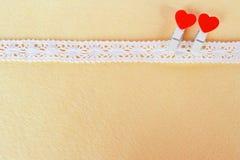 Μπεζ δαντέλλα 2 ξύλινοι γόμφοι με την καρδιά στο μπεζ υπόβαθρο, με το διάστημα για το κείμενο στην ημέρα βαλεντίνων Στοκ φωτογραφίες με δικαίωμα ελεύθερης χρήσης