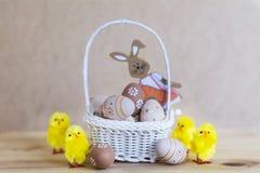 Μπεζ αυγά Πάσχας στο μικρό άσπρο καλάθι με τα κίτρινα κοτόπουλα Στοκ Εικόνα