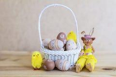 Μπεζ αυγά Πάσχας στο μικρό άσπρο καλάθι με τα κίτρινα κοτόπουλα Στοκ Εικόνες