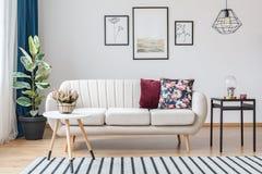 Μπεζ καναπές με τα ξύλινα πόδια στοκ εικόνες με δικαίωμα ελεύθερης χρήσης