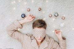 Μπεζ σφαίρες Χριστουγέννων μασκών ύπνου πυτζαμών κοριτσιών στοκ φωτογραφία