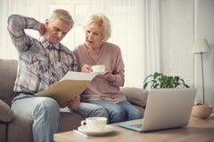 Μπερδεμένοι συνταξιούχοι που κτυπούν τον εγκέφαλό τους με το κληροδότημα στοκ εικόνα με δικαίωμα ελεύθερης χρήσης
