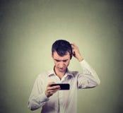 Μπερδεμένος νεαρός άνδρας που εξετάζει το τηλέφωνο που βλέπει τις κακές ειδήσεις ή τις φωτογραφίες Στοκ Εικόνες