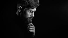 Μπερδεμένος νεαρός άνδρας σχετικά με τη γενειάδα που κοιτάζει κάτω από πέρα από το μαύρο backgro Στοκ Εικόνα