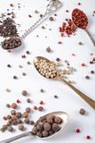 Μπιζέλια μαύρων, κόκκινων, άσπρων πιπεριών στα κουτάλια μετάλλων σε ένα άσπρο υπόβαθρο τσίλι, πάπρικα στοκ φωτογραφία με δικαίωμα ελεύθερης χρήσης