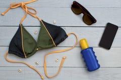Μπικίνι, suntan κρέμα, γυαλιά ηλίου και κινητό τηλέφωνο στο ξύλινο υπόβαθρο στοκ φωτογραφίες