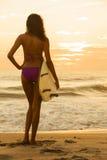 Μπικίνι Surfer κοριτσιών γυναικών & παραλία ηλιοβασιλέματος ιστιοσανίδων Στοκ εικόνες με δικαίωμα ελεύθερης χρήσης