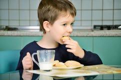 Μπισκότα δαγκωμάτων μικρών παιδιών, που κάθονται στον πίνακα γευμάτων horizont στοκ φωτογραφίες