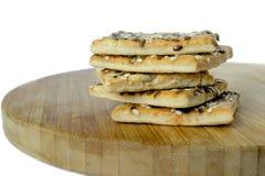 Μπισκότα δημητριακών που συσσωρεύονται ο ένας πάνω από τον άλλον Ξύλινη σανίδα άσπρος Στοκ Φωτογραφία