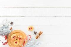 Μπισκότα, κάλαμος καραμελών και Χριστούγεννα που διακοσμούν τα στοιχεία στο άσπρο ξύλο Στοκ Εικόνες