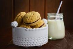 Μπισκότα και γάλα γυαλιού στον ξύλινο πίνακα Στοκ Φωτογραφίες