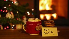 Μπισκότα και καυτή σοκολάτα που προετοιμάζονται για το santa, χέρι που τοποθετεί την κάρτα φιλμ μικρού μήκους