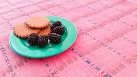 Μπισκότα και μαύρες μουριές σε ένα πιάτο Στοκ Φωτογραφίες