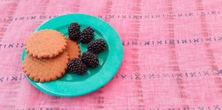 Μπισκότα και μαύρες μουριές σε ένα πιάτο Στοκ Εικόνες