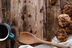Μπισκότα και το φλυτζάνι του τσαγιού στον ξύλινο πίνακα Στοκ Φωτογραφίες