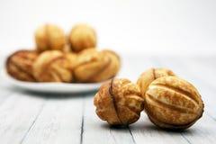 Μπισκότα - καρύδια σε έναν ξύλινο πίνακα, δίπλα σε ένα πιάτο με τις θολωμένες ζύμες στοκ εικόνα με δικαίωμα ελεύθερης χρήσης