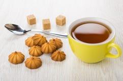 Μπισκότα κουλουρακιών, φλυτζάνι του τσαγιού, άμορφα ζάχαρη και κουταλάκι του γλυκού Στοκ Εικόνα
