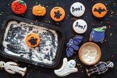 Μπισκότα μελοψωμάτων αποκριών μαγείρων με το ρόπαλο, σκελετός, γλυκά φαντασμάτων κοντά στο φύλλο ψησίματος Μαύρη τοπ άποψη υποβάθ Στοκ φωτογραφία με δικαίωμα ελεύθερης χρήσης