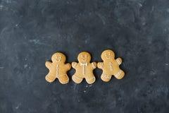Μπισκότα μελοψωμάτων σε ένα γκρίζο υπόβαθρο τα μπισκότα Χριστουγέννων βρίσκουν ότι οι εικόνες φαίνονται περισσότερο οι ίδιες σειρ Στοκ φωτογραφία με δικαίωμα ελεύθερης χρήσης