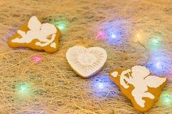 Μπισκότα μελοψωμάτων υπό μορφή cupids και καρδιών Πολύχρωμη γιρλάντα Στοκ Φωτογραφίες