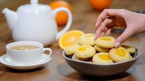 Μπισκότα με την πορτοκαλιά μαρμελάδα Τεθειμένος στα πορτοκαλιά μπισκότα κύπελλων φιλμ μικρού μήκους