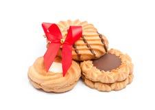 Μπισκότα με τη σοκολάτα και την κόκκινη κορδέλλα στην άσπρη ανασκόπηση Στοκ Εικόνα