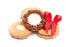 Μπισκότα με τη σοκολάτα και την κόκκινη κορδέλλα στην άσπρη ανασκόπηση Στοκ φωτογραφία με δικαίωμα ελεύθερης χρήσης