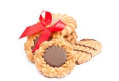 Μπισκότα με τη σοκολάτα και την κόκκινη κορδέλλα στην άσπρη ανασκόπηση Στοκ φωτογραφίες με δικαίωμα ελεύθερης χρήσης