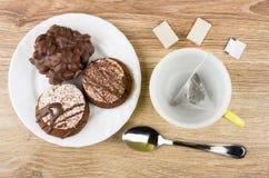 Μπισκότα με τη σοκολάτα στο πιάτο, φλυτζάνι με teabag, ζάχαρη Στοκ εικόνες με δικαίωμα ελεύθερης χρήσης