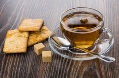 Μπισκότα με τη σταφίδα, το φλυτζάνι του τσαγιού, την άμορφα ζάχαρη και το κουταλάκι του γλυκού Στοκ Εικόνες
