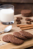 Μπισκότα με το ποτήρι του γάλακτος στο φυσικό ξύλινο πίνακα Στοκ Φωτογραφία