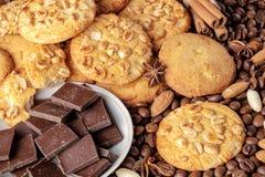 Μπισκότα με το φυστίκι, πιατάκι με τα κομμάτια της σοκολάτας και διεσπαρμένα φασόλια καφέ Στοκ Εικόνες