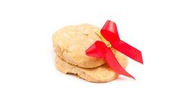 Μπισκότα με macadamia το καρύδι και την κόκκινη κορδέλλα στο άσπρο backgroun Στοκ φωτογραφία με δικαίωμα ελεύθερης χρήσης