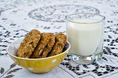 Μπισκότα μπισκότων Anzac που γίνονται από το πρόχειρο φαγητό βρωμών με το ποτήρι του γάλακτος Στοκ Εικόνες