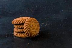 Μπισκότα που συσσωρεύονται σε ένα μαύρο υπόβαθρο Στοκ Φωτογραφία